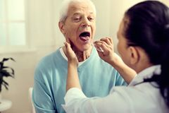 Medical worker checking tonsils of elderly gentleman. Looking good. Selective focus on a serene retired men sitting in a hospital while checking his tonsils and royalty free stock images