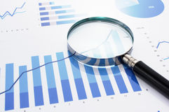 Looking at growth chart with magnifying glass. Stock Photo