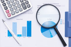Looking at growth chart with magnifying glass. Graphs, charts an. D magnifying glass Stock Image