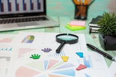 Looking at growth chart with magnifying glass. Graphs, charts an. Business Desktop. Looking at growth chart with magnifying glass. Graphs, charts and magnifying royalty free stock images