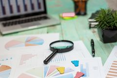 Looking at growth chart with magnifying glass. Graphs, charts and magnifying glass. Business Desktop. Looking at growth chart with magnifying glass. Graphs royalty free stock images