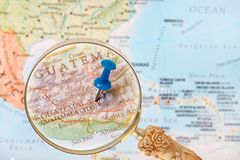 Looking in on Guatemala City. Blue tack on map of Central America with magnifying glass looking in on Guatemala City, Gatemala Royalty Free Stock Photos