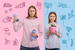 Sporty man holding hand weights and a loving wife standing with a flowerpot. Looking healthy. Serious strong husband holding hand weights while his pretty stock image