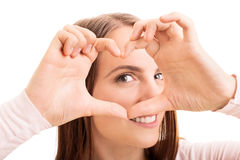 Looking through the heart. Beauty portrait of a young girl looking through a heart shaped hands Stock Photos