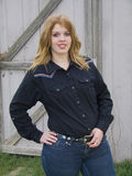 Looking for Her Cowboy. Curvy alluring young cowgirl standing by the barn Royalty Free Stock Photo