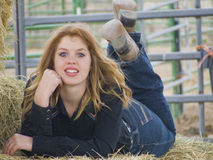 Looking for Her Cowboy. Curvy alluring young laying in the hay Stock Photo