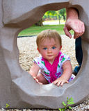 Looking through the hole. One year old playing on playground. Looking through a hole in a rock climbing wall as her father points the direction to go through Royalty Free Stock Photos