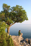 Looking into horizon. Man sitting on the rock under the tree and looking into horizon Royalty Free Stock Photos