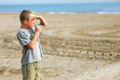 Looking hungry 4. Young boy is watching the scenery at the beach and is eating a hamburger royalty free stock image