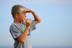 Looking hungry 5. Young boy is watching the scenery at the beach and is eating a hamburger royalty free stock photo