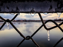 Looking through ice covered chain link fence at sunset and other side of Illinois river Royalty Free Stock Images