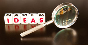 Looking for ideas. Text ' ideas ' in red uppercase letters on white cubes with hand magnifier dark background Stock Photo