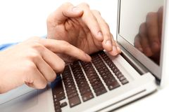 Looking for information. Close-up of male hand over laptop keyboard while the other one hiding forefinger Royalty Free Stock Photo