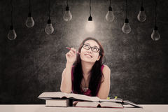 Looking for inspiration. Beautiful student is looking for inspiration or ideas under light bulbs Stock Images