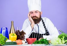 Looking for inspiration. Bored chef lean on table at kitchen. Culinary inspiration. Hard day at restaurant. Tired and. Exhausted chef. Man bearded chef cooking stock photography