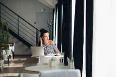 Looking for inspiration. Young beautiful pensive woman making some notes and looking through window while sitting in Royalty Free Stock Photos