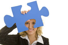 Looking through a jigsaw piece. Blonde business woman looking through an oversized jigsaw piece Royalty Free Stock Images