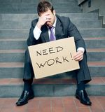 Looking for a job. Desperate businessman holding cardboard sign Stock Photography