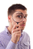 Looking for a job. Young man through Magnifying glass, isolated on white Stock Photos