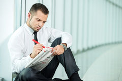 Looking for a job. The concept of job search. A man is sitting with a newspaper Royalty Free Stock Images