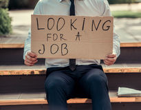 Looking for a job. Cropped image of businessman holding a cardboard sheet with phrase `looking for a job` while sitting on stairs outdoors Royalty Free Stock Images