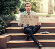 Looking for a job. Handsome businessman is holding a cardboard sheet with phrase `looking for a job` and looking at camera while sitting on stairs outdoors Royalty Free Stock Images
