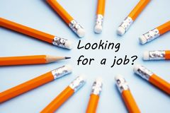 Looking for a job inscription. Yellow office pencils over blue background. Finding a job, looking for a job concept. Looking for a job inscription. Yellow royalty free stock images