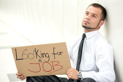 Looking for a job. Unemployment. Young businessman is squatting with sign Looking for a job, outdoors Stock Photo