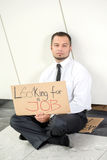 Looking for a job. Unemployment. Young businessman is squatting with sign Looking for a job, outdoors Royalty Free Stock Image