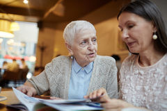 Looking through journal. Senior women talking to her friend while both looking through magazine royalty free stock photography