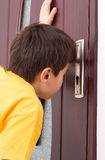 Looking through keyhole. Indecency concept - Boy looking through keyhole Stock Photos