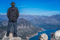 Looking at the Kotor bay from above. Tourist with a hat standing on a large boulder and admiring the stunning landscape of the Bay of Kotor in Montenegro as seen stock photos