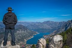 Looking at the Kotor bay from above. Tourist with a hat standing on a large boulder and admiring the stunning landscape of the Bay of Kotor in Montenegro as seen stock photo