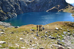 Looking the lake. Three trekkers looking lago superiore in formazza valley Royalty Free Stock Photo