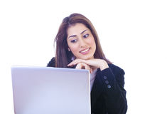 Looking at laptop. Pretty girl looking at laptop screen with interest and a smile Royalty Free Stock Photography