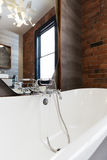 Looking into large white freestanding vintage bath tub. With vintage style tap ware stock photo