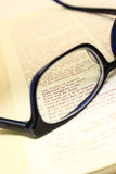 Looking Through the Lens of Glasses. Bible open to lord's prayer displayed through a pair of glasses Royalty Free Stock Image