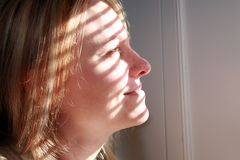 Looking into the Light. A beautiful and happy young woman looks out a window Stock Photography