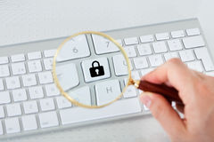 Looking at lock key through magnifying glass Stock Photos