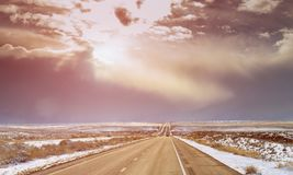 Looking a long road in New Mexico, with snow mountains in the distance. Looking along a long road in New Mexico, with snow mountains in the distance royalty free stock image