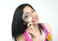 Looking through the magnifying glass. Pretty young asian girl looking through a hand lens Royalty Free Stock Photography