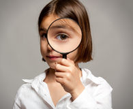 Looking through magnifying glass Stock Photography