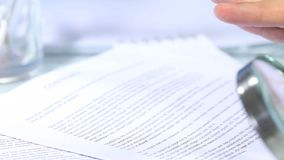 Looking through a magnifying glass to contract and hand signature stock footage