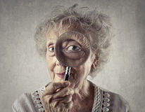 Looking into a magnifying glass. Woman looking into a magnifying glass Royalty Free Stock Photo