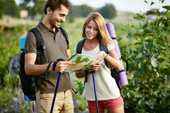 Looking at map. Portrait of couple of hikers looking at map in the countryside at summer Stock Photo