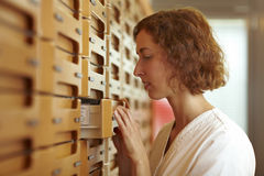 Looking in medicine cabinet. Female pharmacist at medicine cabinet in pharmacy royalty free stock photography