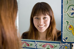 Looking in Mirror. Attractive young woman seen as a reflection in an ethnic style mirror Stock Images