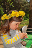 Looking in the mirror. Little girl wearing dandelion diadem looking in the mirror Stock Images