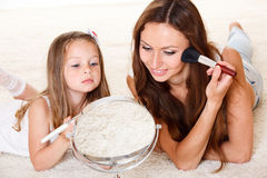 Looking into mirror. Young women and little girl looking into mirror Stock Photos
