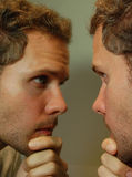 Looking in the Mirror. Portrait of an attractive man looking in the mirror Stock Images